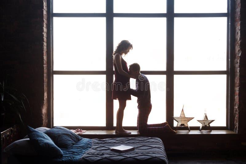 Silhouet van jong gelukkig mooi paar die baby het verenigen in de grote venstervensterbank verwachten zich Echtgenoot die zich op royalty-vrije stock fotografie