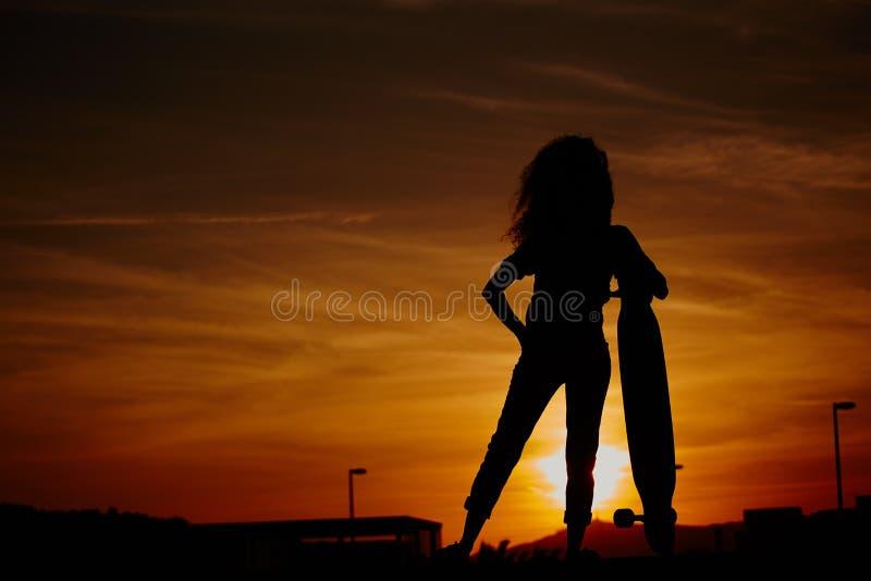 Silhouet van jong hipstermeisje met een longboard in zonsondergang stock fotografie