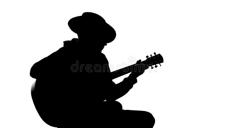 Silhouet van jong mannetje in hoed het spelen gitaar bij partij, koele hobby, recreatie royalty-vrije stock afbeelding
