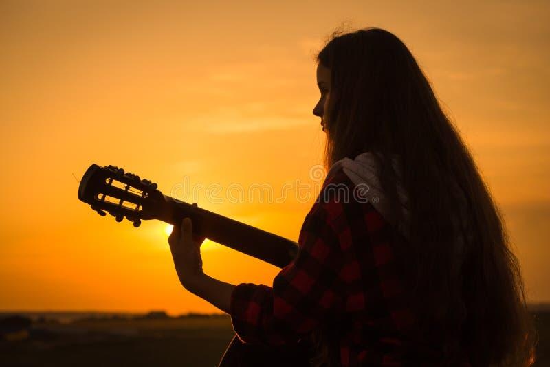 Silhouet van jong meisje die de gitaar spelen bij zonsondergang stock fotografie