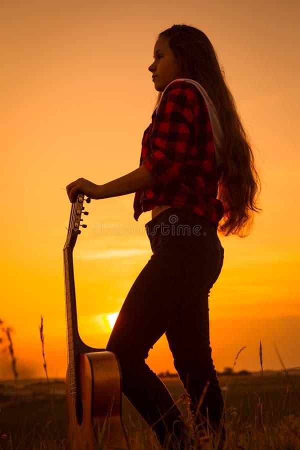 Silhouet van jong meisje met gitaar bij zonsondergang stock foto