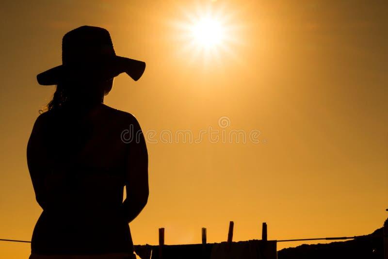 Silhouet van jong meisje met hoed, zonsondergang royalty-vrije stock afbeeldingen