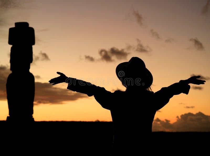 Silhouet van jong wijfje die haar wapens opheffen die indrukwekkende zonsonderganghemel met Moai-standbeeld bewonderen in Ahu Tah stock fotografie