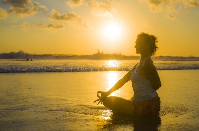 Silhouet van jonge geschikte en aantrekkelijke sportvrouw in van de de yogapraktijk van de strandzonsondergang de trainingzitting royalty-vrije stock afbeeldingen