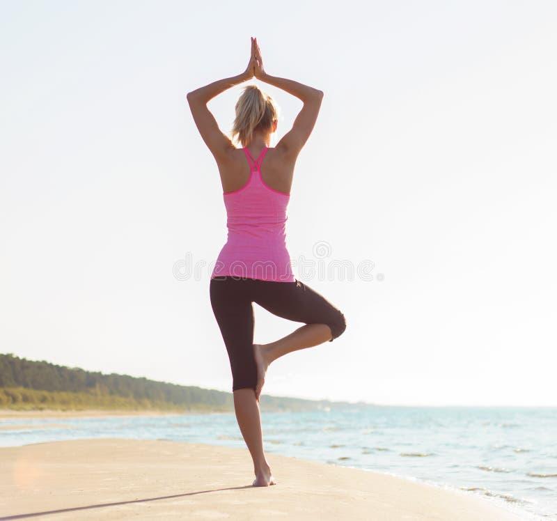 Silhouet van jonge gezonde en geschikte vrouw het praktizeren yoga royalty-vrije stock afbeeldingen