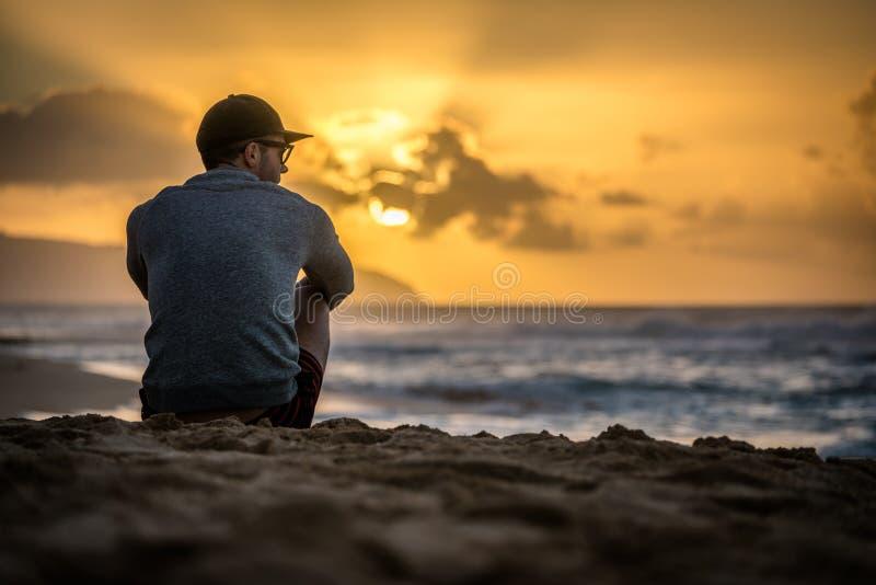 Silhouet van jonge Kaukasische mannelijke zitting op Zonsondergangstrand die uit zonsondergang over de oceaan bekijken stock foto