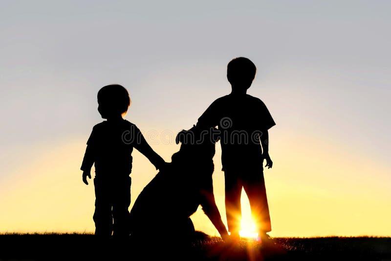 Silhouet van Jonge Kinderen met Hond stock foto's