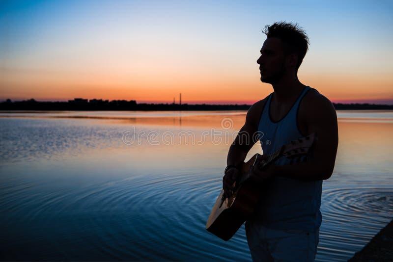 Silhouet van jonge knappe mens het spelen gitaar bij kust tijdens zonsopgang outdoors royalty-vrije stock foto