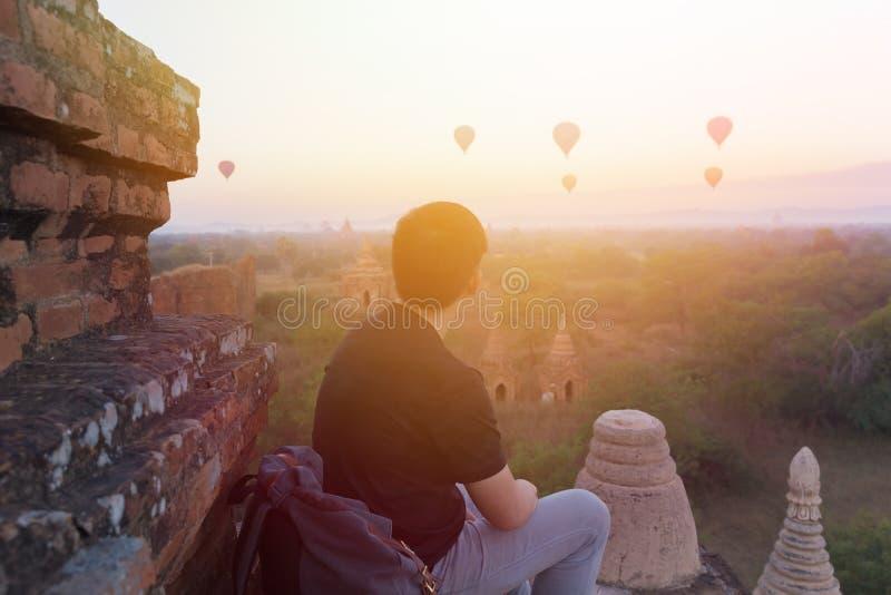 Silhouet van jonge mannelijke backpacker die en de reis op bestemmingen van de hete luchtballon in Bagan, Myanmar zitten letten stock afbeelding