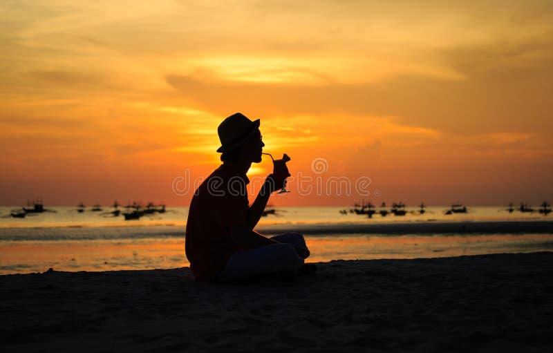 Silhouet van jonge mens het drinken cocktail bij royalty-vrije stock fotografie