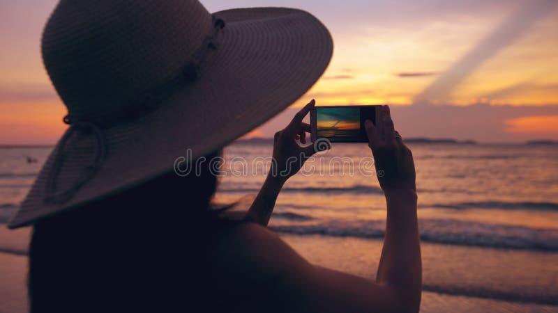 Silhouet van jonge toeristenvrouw in hoed die foto met cellphone nemen tijdens zonsondergang in oceaanstrand royalty-vrije stock foto