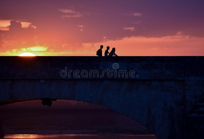Silhouet van jonge vrienden op een kleurrijke zonsondergang wanneer het terugkeren van huis, die een brug kruisen stock foto