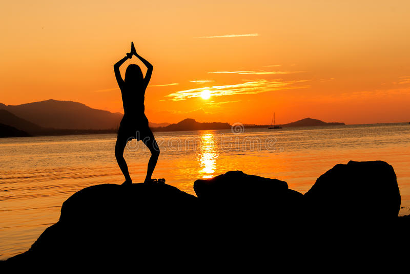 Silhouet van jonge vrouw het praktizeren yoga royalty-vrije stock foto