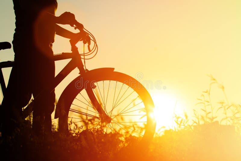 Silhouet van jonge vrouwen berijdende fiets bij zonsondergang royalty-vrije stock afbeeldingen