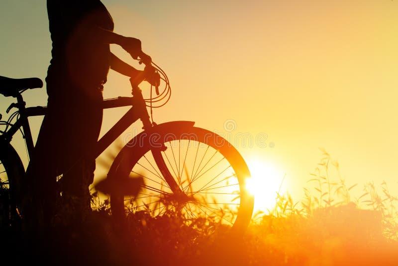 Silhouet van jonge vrouwen berijdende fiets bij zonsondergang royalty-vrije stock foto