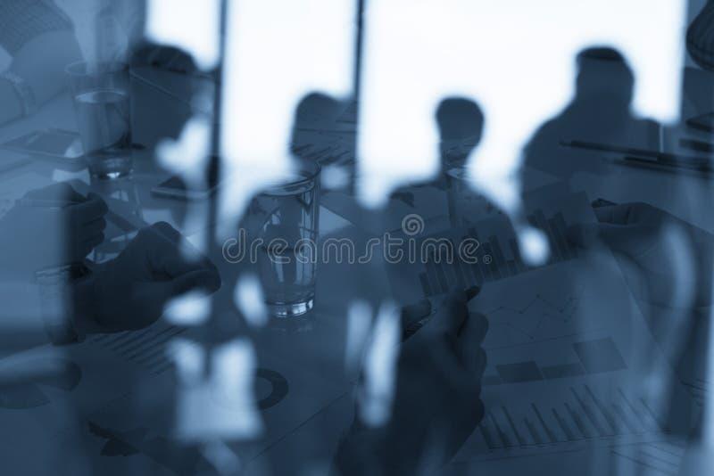 Silhouet van jonge werknemers in het bureau met statistiekaantekenvellen concept groepswerk en zaken Dubbele blootstelling royalty-vrije stock afbeelding