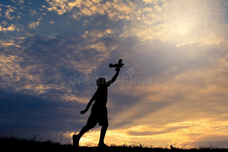 Silhouet van jongen die houten vliegtuig in aard spelen stock foto's
