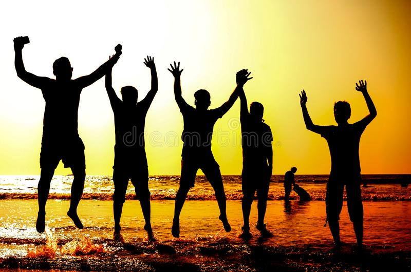 Silhouet van jongeren die op het overzeese strand springen royalty-vrije stock foto's