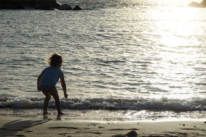 Silhouet van kind het lopen en een spel op het strand bij zonsondergang royalty-vrije stock fotografie