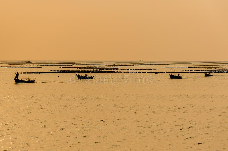 Silhouet van Kleine vissersboten op het overzees tijdens zonsondergang royalty-vrije stock foto's