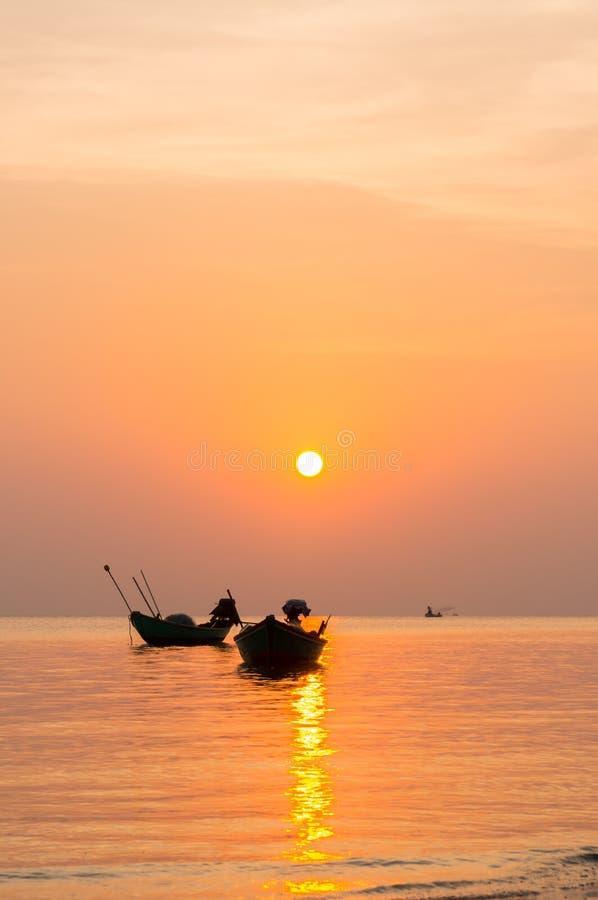 Silhouet van Kleine vissersboten op het overzees tijdens zonsopgang stock afbeeldingen