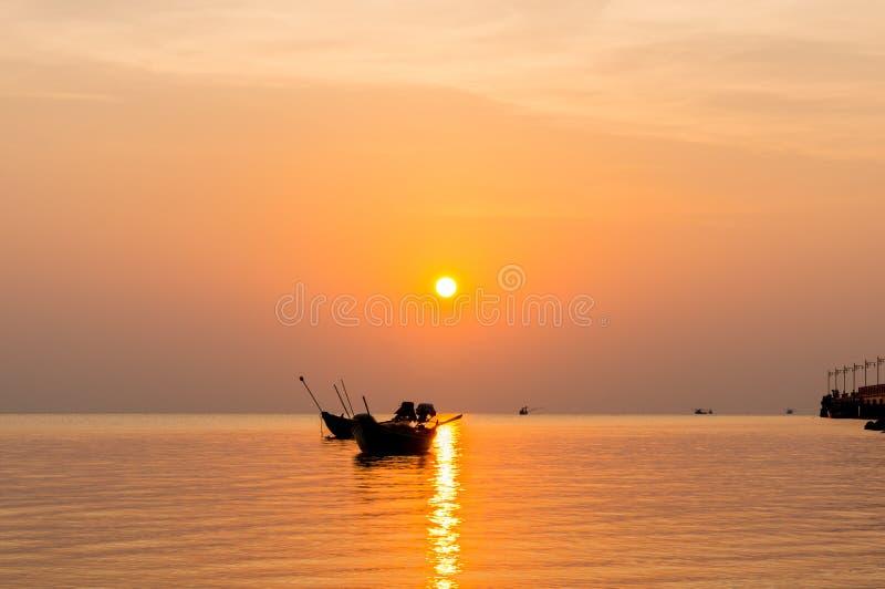 Silhouet van Kleine vissersboten op het overzees tijdens zonsopgang stock afbeelding