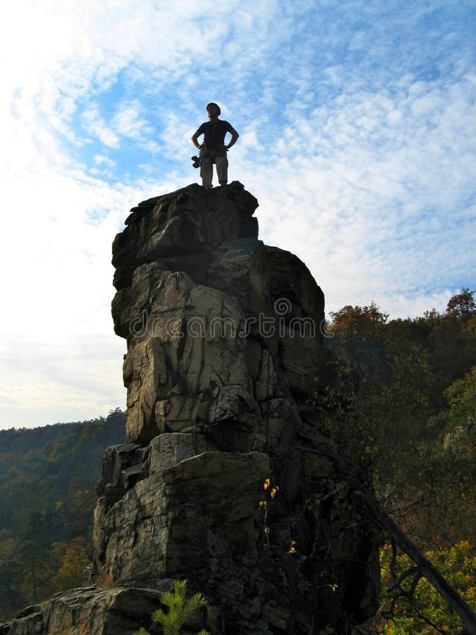 Silhouet van klimmer op de bovenkant van rotstoren royalty-vrije stock afbeeldingen