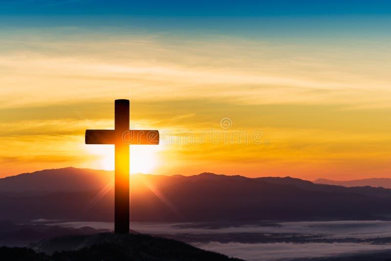 Silhouet van kruis op de achtergrond van de bergzonsondergang royalty-vrije stock foto