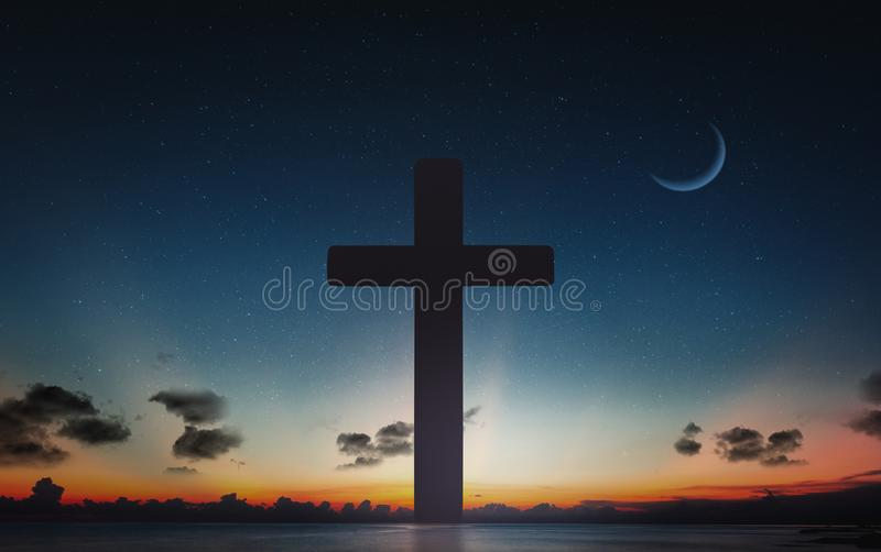 Silhouet van kruisbeeldkruis bij van de zonsondergangtijd en nacht hemel met maanachtergrond stock foto