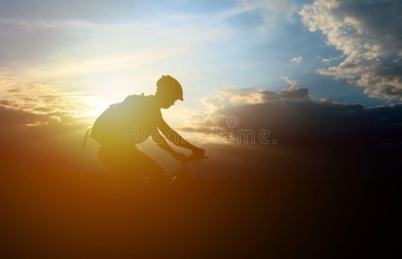 Silhouet van mannelijk mountainbiker bij zonsondergang stock afbeelding