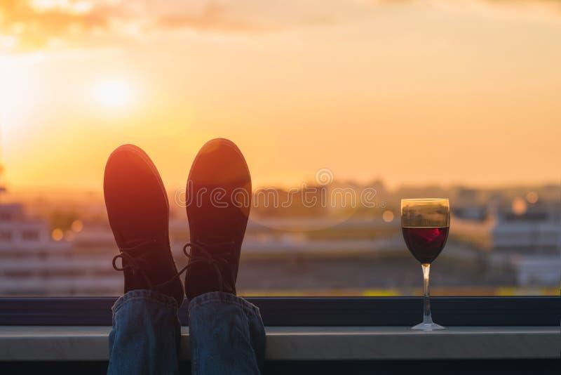 Silhouet van mannelijke voeten in de schoenen met glas rode wijn op de achtergrond van de zonsondergangstad stock foto