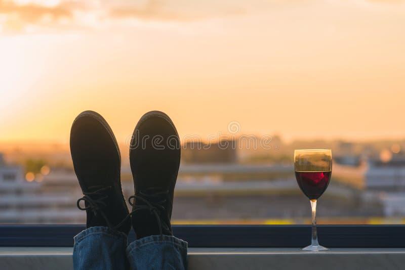 Silhouet van mannelijke voeten in de schoenen met glas rode wijn op de achtergrond van de zonsondergangstad stock foto's