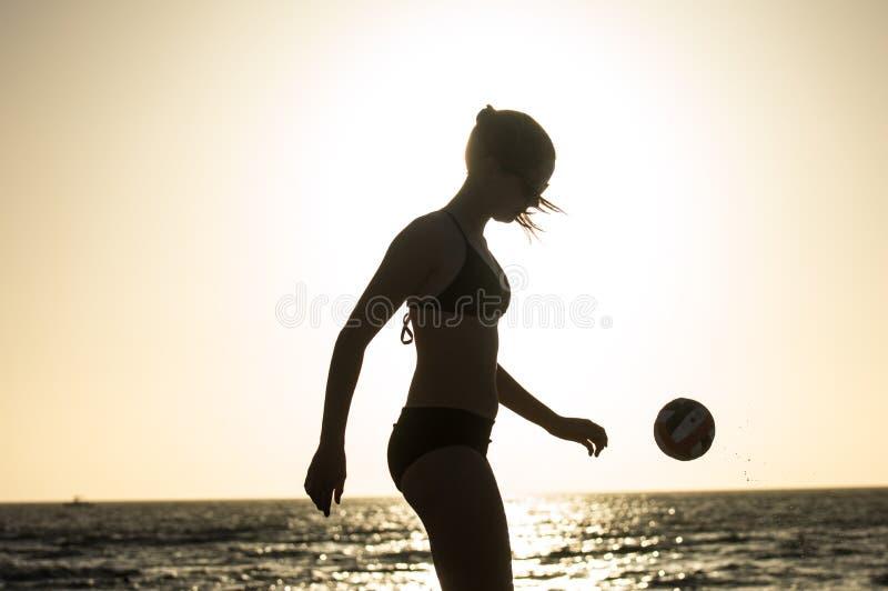 Silhouet van meisje die met een voetbalbal jongleren royalty-vrije stock fotografie