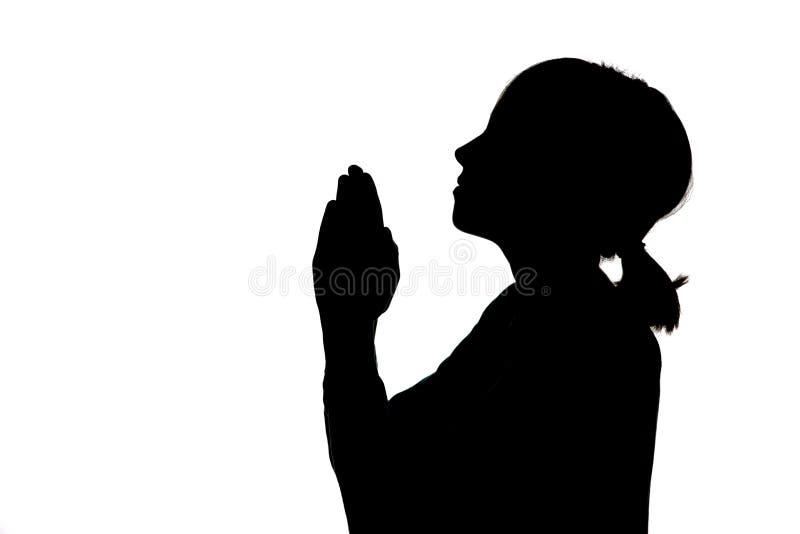Silhouet van meisje het bidden stock foto's