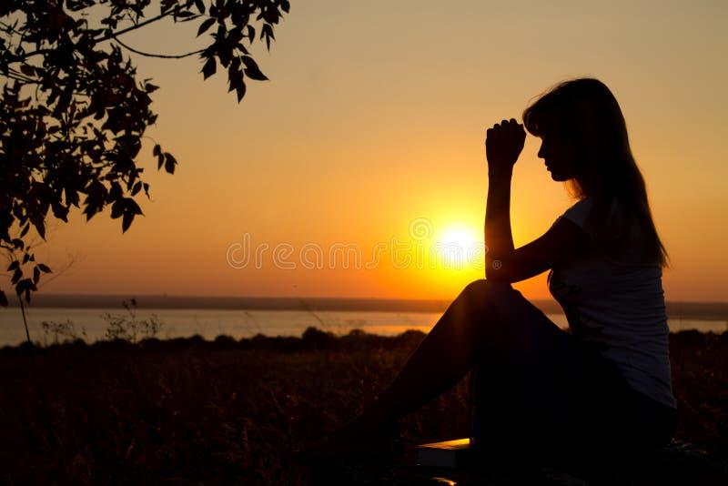Silhouet van meisje het bidden royalty-vrije stock afbeeldingen