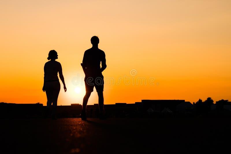 Silhouet van meisje het kijken omhoog aan jongen op de achtergrond van de zonsonderganghemel royalty-vrije stock fotografie