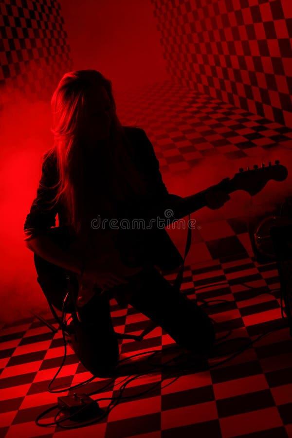 Silhouet van meisje het knielen en het spelen van elektrische gitaar royalty-vrije stock foto's