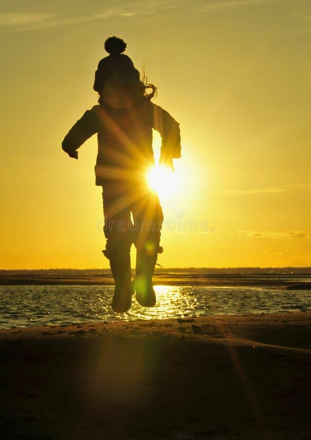 Silhouet van Meisje het springen op de oceaankust in backlightzonsondergang royalty-vrije stock afbeelding
