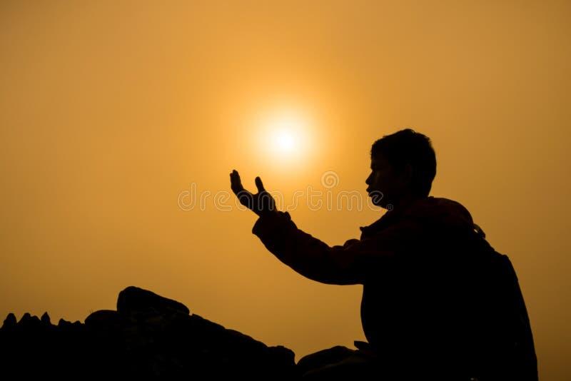 Silhouet van mens die en over mooie zonsopgangachtergrond knielen de bidden royalty-vrije stock afbeeldingen