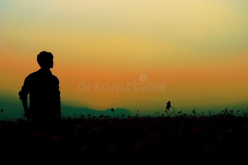 Silhouet van mens het stellen bij zonsonderganghemel royalty-vrije stock afbeelding
