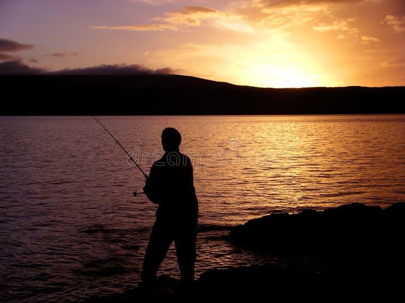 Silhouet van mens overzeese visserij bij zonsondergang stock fotografie