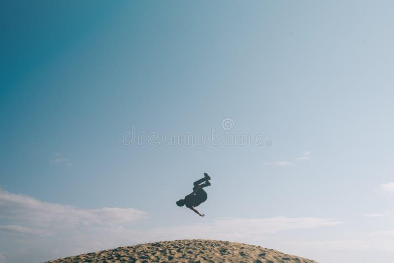 Silhouet van mensen die een acrobatische backflipbeweging op zandduinen doen royalty-vrije stock afbeelding