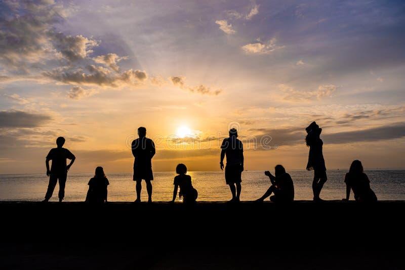 Silhouet van mensen die het letten op kleurrijke zonsopgang ontspannen bij een strand royalty-vrije stock afbeelding