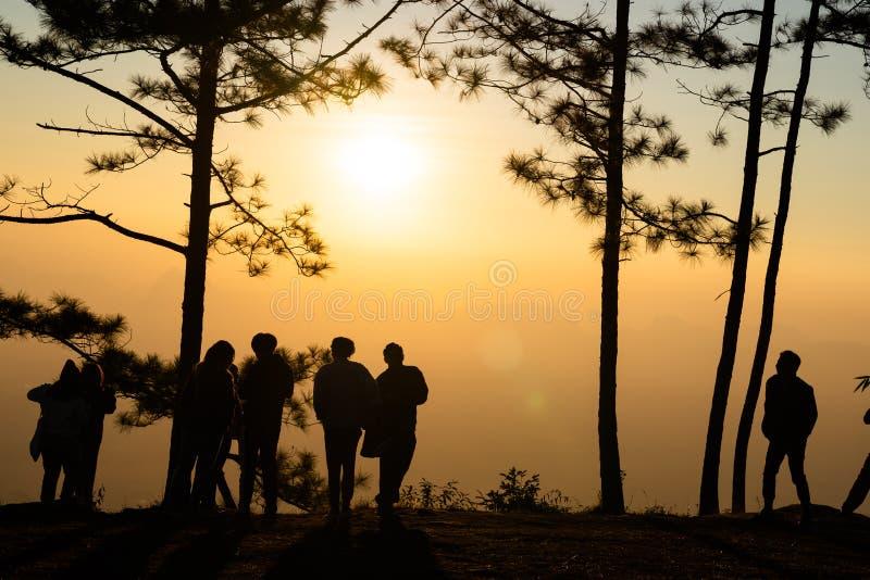 Silhouet van mensen die op de zonsopgang op kleurrijke horizon letten stock afbeelding