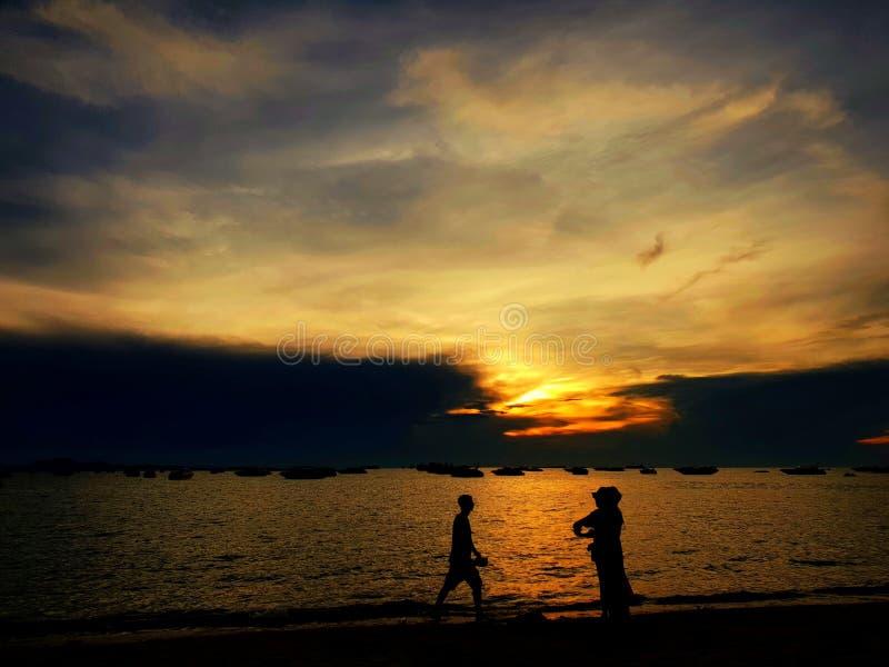 Silhouet van mensen die zonsondergangstrand in de zomervakantie hebben stock foto