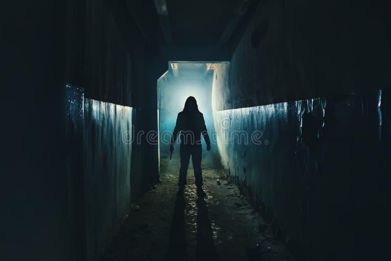 Silhouet van mensenmaniak of moordenaar of verschrikkingsmoordenaar met mes in hand in donkere griezelige en griezelige gang Misd stock fotografie