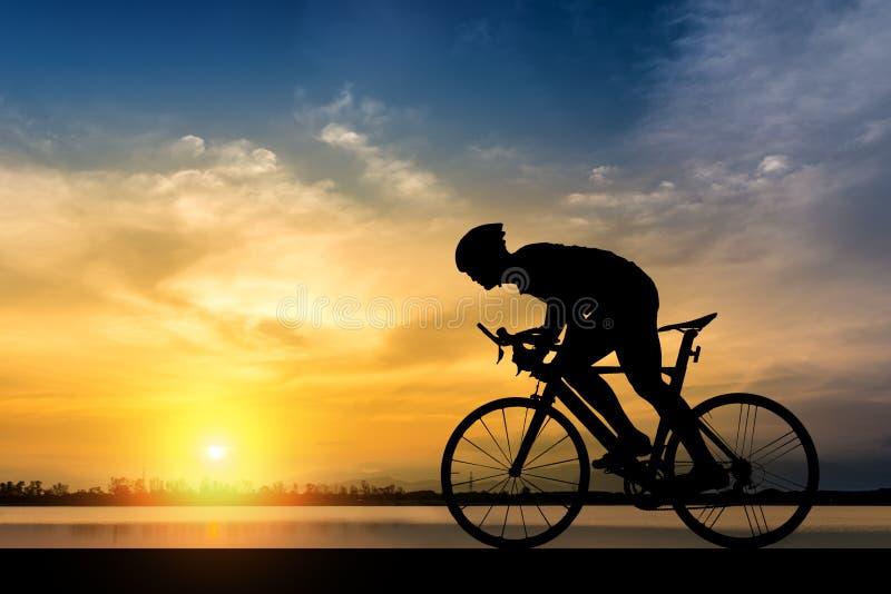 Silhouet van mensenrit een fiets op zonsondergangachtergrond stock fotografie