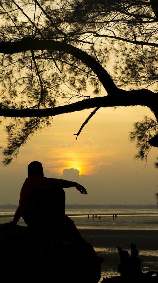 Silhouet van mensenzitting op de rots die de zon zoeken royalty-vrije stock afbeelding