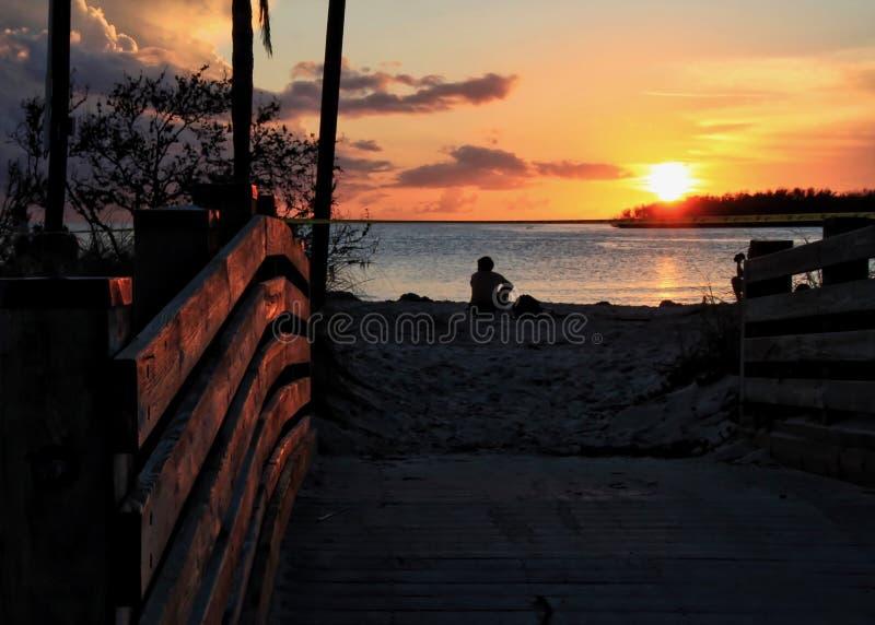 Silhouet van mensenzitting in zand die op een diepe oranje zonsondergang letten over horizon bij Sombrerostrand in Marathonsleute royalty-vrije stock foto