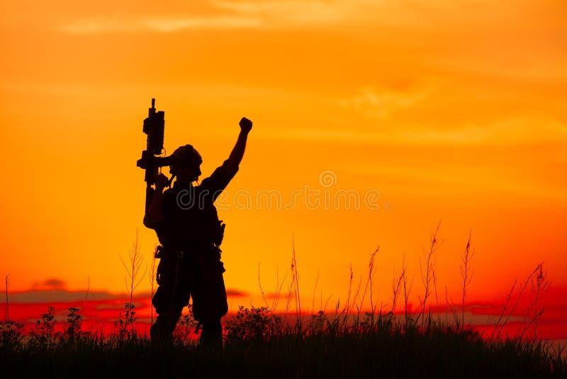 Silhouet van militaire militair of ambtenaar met wapens bij zonsondergang stock illustratie